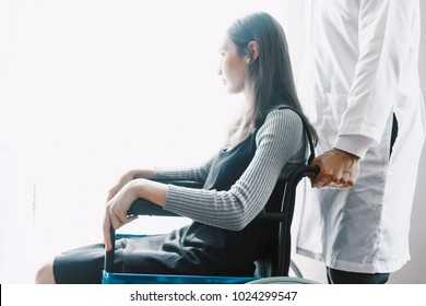 Doctor and female patient in wheelchair sitting in hospital