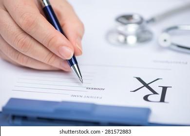 Doctor filling in empty medical prescription on electrocardiogram (ECG) chart