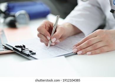 Doctor filling out patients medical history in office closeup. Collecting anamnesis concept