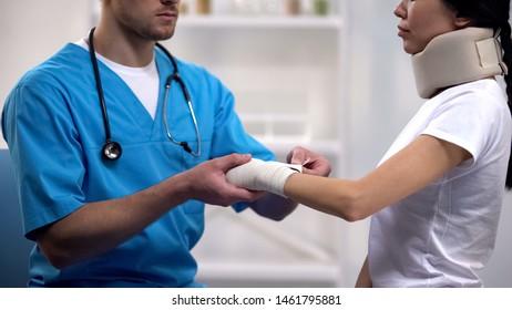 Doctor fixing wrist elastic wrap female patient in foam cervical collar, rehab