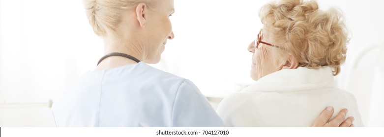 Doctor gently patting her senior patient on the back while smiling at her