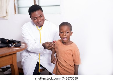 At the doctor. The doctor gives candy to the child