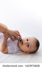 A doctor gives newborn baby rotavirus vaccine. Child immunization with little drop in clinic. Baby boy gets medicine from a little bottle. Immunization, Vaccination, Health concept.