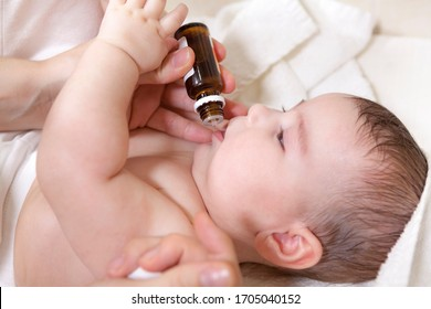 A doctor gives newborn baby vitamin D3. Child immunization with drop in a clinic