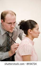 Doctor giving checkup to hispanic woman
