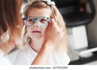 Doctor giving the child new glasses for her vision.