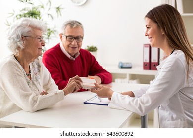 Doctor giving drugs to her senior woman patient, closeup