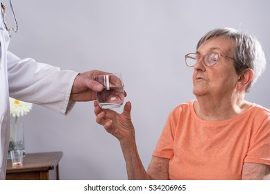 Doctor giving a glass of water to an elderly patient