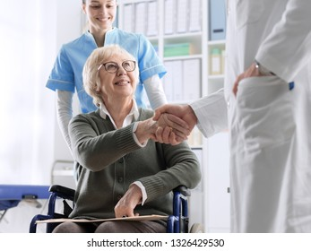 Doctor giving an handshake to a smiling senior female patient and caring nurse, healthcare and trust concept