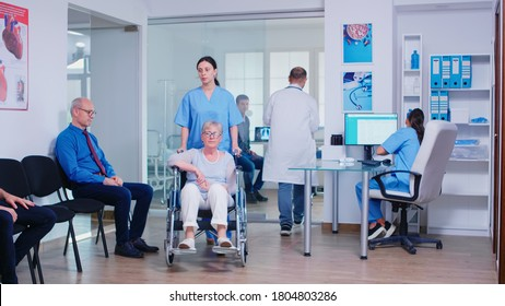 Doctor giving nurse radiography of sick patient. Medical assistant and invalid senior woman in wheelchair. Old man in clinic waiting area. Health care system and medical consultation