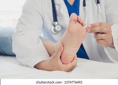 Ärztin, die eine Fußbehandlung bei einem Patienten durchführt