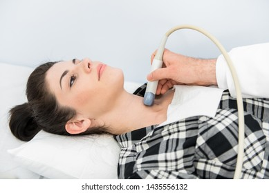 Doctor Giving Patient An Ultra Sound-young woman getting thyroid gland control