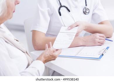 Doctor giving the prescription to the elder patient