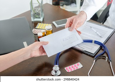 Doctor giving a prescription to his patient in medical office