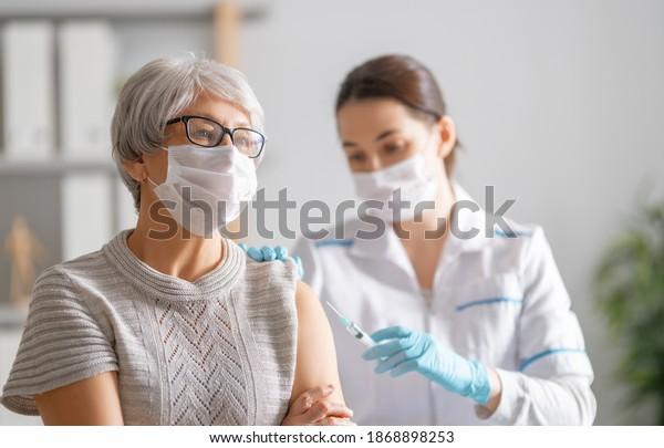 Doctor vacunando a una anciana. Protección contra virus. COVID-2019.