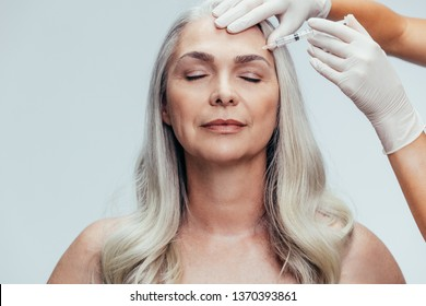 Doctor with gloves injecting with an needle into temple of the senior woman against grey background. Woman getting anti aging injection on her face to reduce wrinkles.