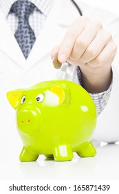 Doctor with green piggy bank as an idea for healthcare insurance and savings for medical expenses