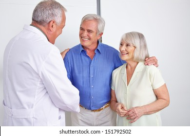 Doctor greeting happy senior couple with a handshake in a hospital