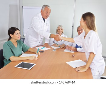 Doctor greeting new colleague in team with handshake