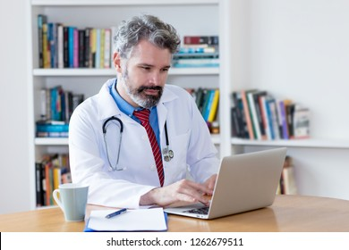 Doctor with grey hair working with computer at hospital