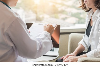 Doctor (gynecologist or psychiatrist) consulting and examining woman patient's health in medical clinic or hospital healthcare service center
