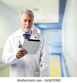 Doctor in the hallway of the hospital with tablet