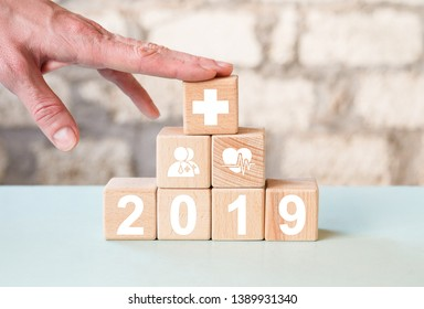 Doctor hand arranging wood block stacking with icon 2019 year healthcare medical, insurance for your health concept.