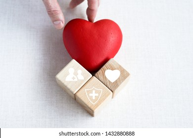 Doctor hand arranging wood block stacking with icon health care medical, insurance for your health concept.