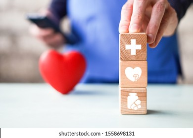 Doctor hand arranging wood block stacking with healthcare icons, insurance for your health.