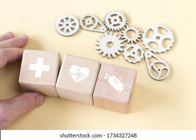 Doctor hand arranging wood block stacking with healthcare icons, insurance for your health, on the background of gears.