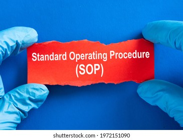 Doctor hand in blue glove with word Standard Operating Procedure (SOP).  Coronavirus Medical Concept.