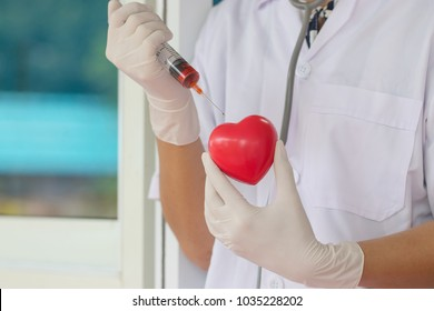 Doctor hand hold red heart shape with stethoscope hang in neck and hold vaccine syringe. Research in laboratory for heart disease. Healthy and science concept. Soft focus and blur green nature.