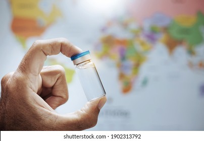 Doctor hand holding flu, measles, coronavirus, covid-19 vaccine disease preparing for people all over the world. vaccination shot, medicine and drug concept with blurred world map background