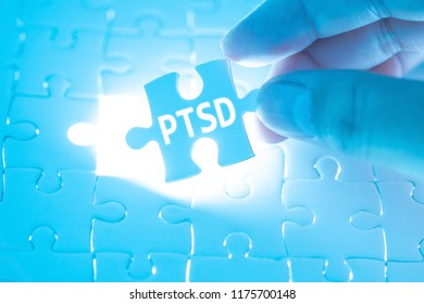 Doctor hand holding a jigsaw puzzle with PTSD - post traumatic stress disorder. War veteran mental health issue word. Concept Healthy.