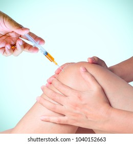 Doctor hand holding syringe of platelet rich plasma for injection to knee.