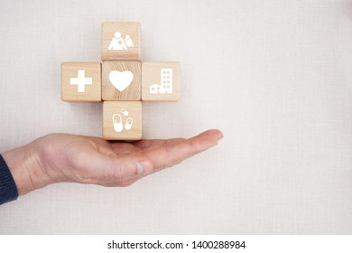 Doctor hand holds wood block stacking with icon healthcare medical, insurance for your health concept.