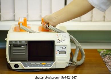 Doctor hand takes electroshock probes in hospital cabinet, noface