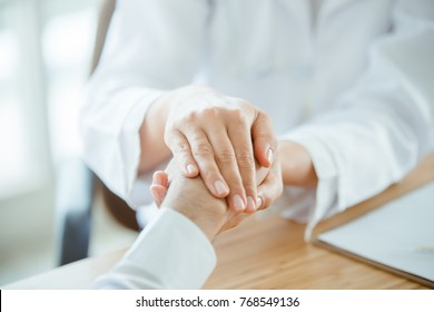 The doctor handles her patient's hand. To be grateful