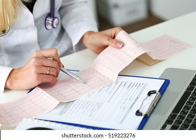 Doctor hands with cardiogram chart on clipboard pad fill medical history with silver pen. Cardio therapeutist assistance, physician make cardiac physical, pulse measure document, arrhythmia idea