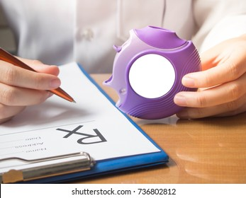 Doctor hands holding medicine dry powder inhaler and writing medical prescription on rx form for treatment asthma/COPD diseases on physician's desk at hospital. Health care and medication concept.