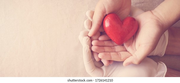 Doctor hands with medical gloves holding child hands and red heart, health insurance, donation, charity during covid-19 coronavirus pandemic, saving life, thank you and appreciation to doctor