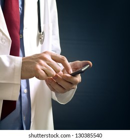 Doctor hands with mobile phone. Male doctor in white coat is using a modern smartphone device with touch screen.