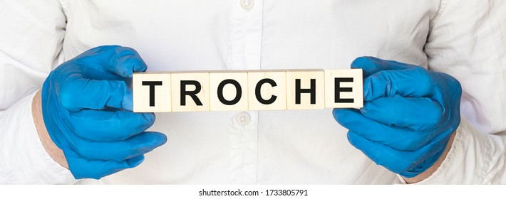 Doctor hands with wood block with TROCHE text