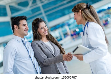 Doctor handshaking with a couple at the hospital