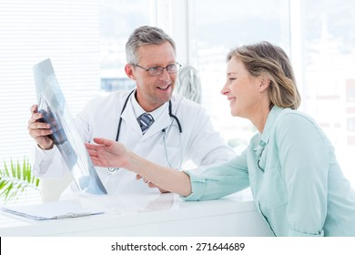 Doctor having conversation with his patient and holding xray in medical office