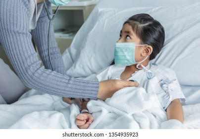 doctor heal Influenza A virus or H1N1 flu asian kid on hospital bed. Medicine virus situation when kid have high fever. Doctor use stethoscope to hear pulp