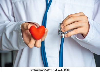 A doctor or healthcare professional holds heart shape in one hand and stethoscope in other. Concept photo for diagnosing and determining the causes of the onset of heart and cardiovascular diseases