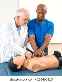 Doctor helping an adult student learn CPR.