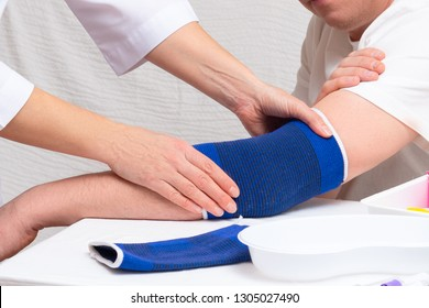 doctor helps the patient to use bandage on the elbow