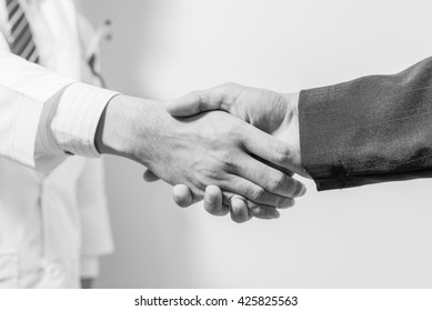 doctor and her lawyer shaking hands. handshake Business and doctor concept.